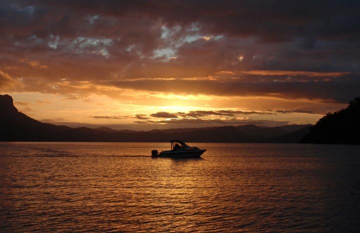 Boat on Lake Waikaremoana at sunset, New Zealand