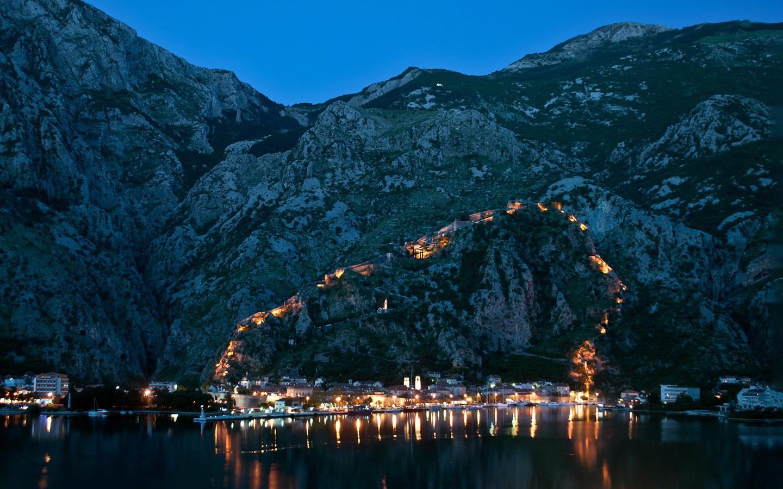 Kotor city walls lit up at night