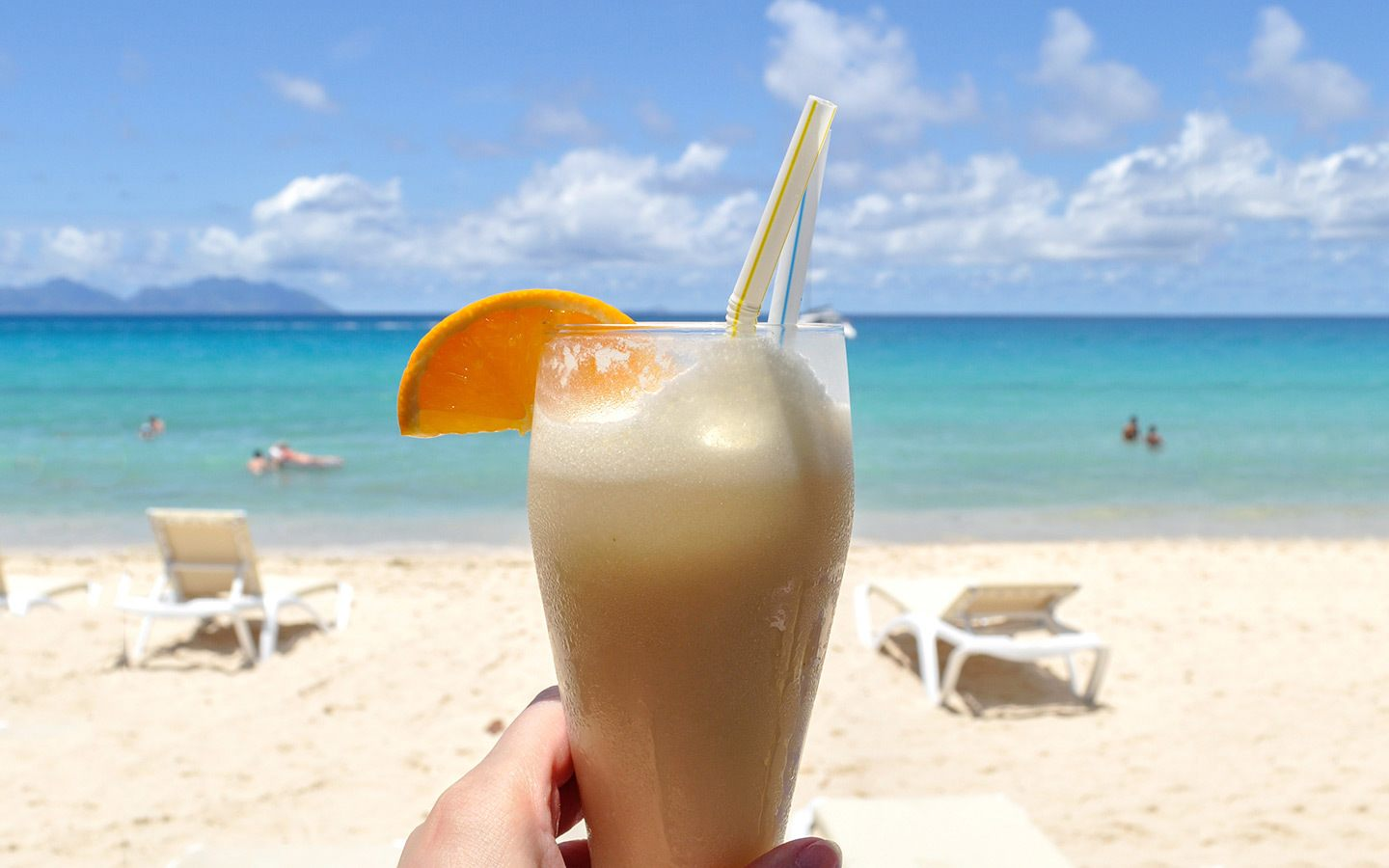 Cocktail on the beach while reading books for travellers