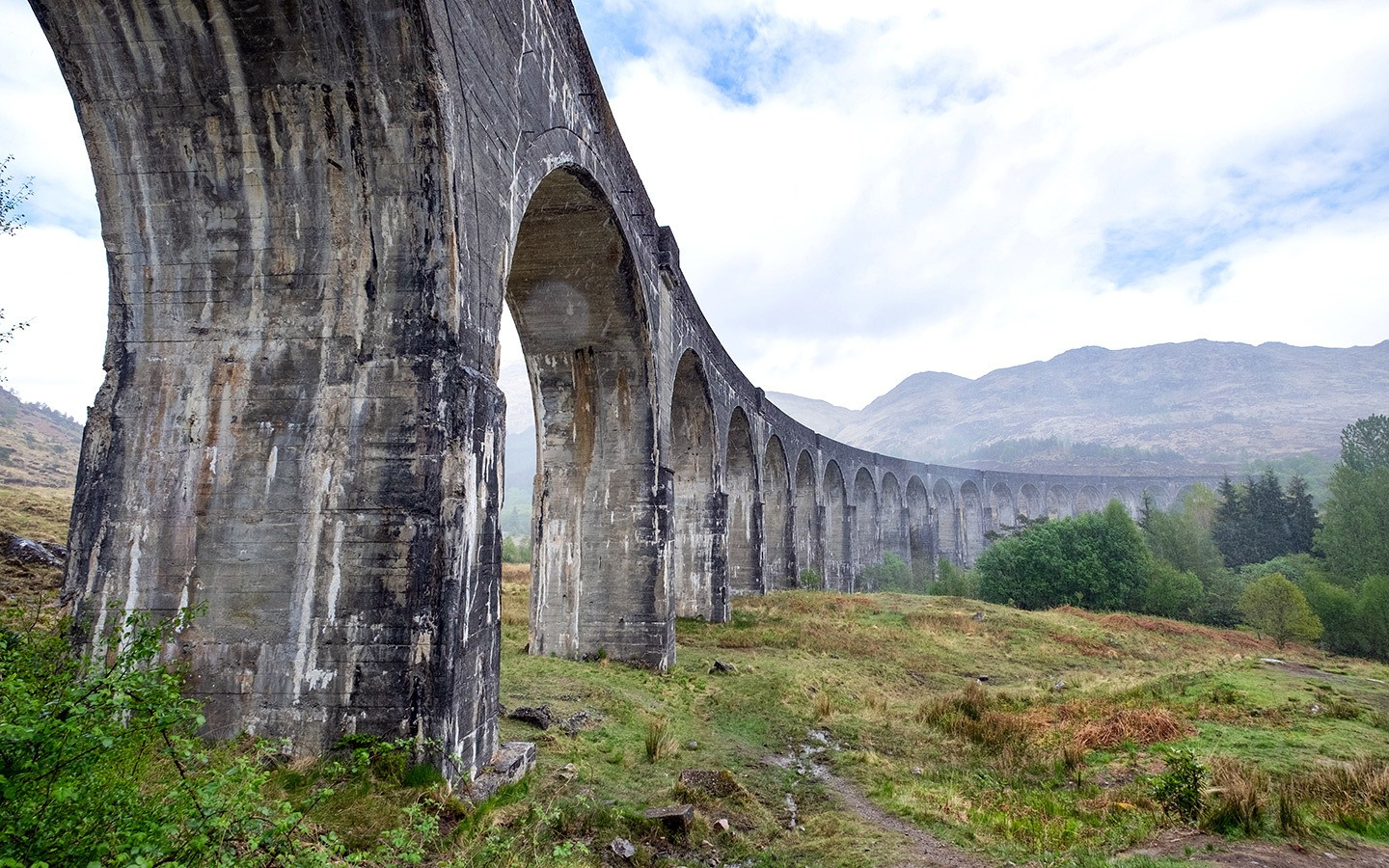 The Jacobite steam train crosses the Glenfinnan Viaduct in Scotland