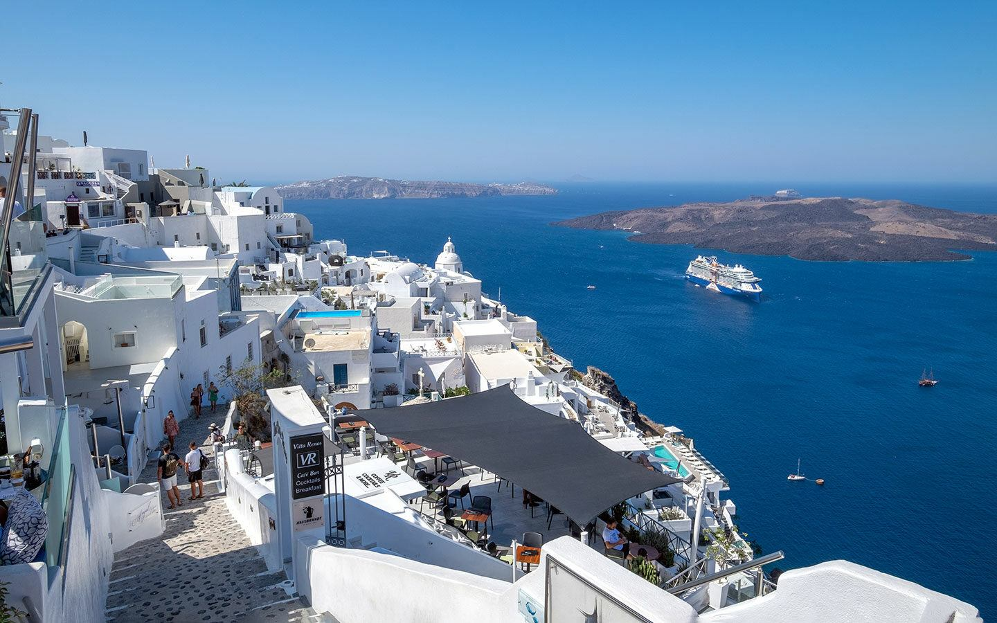 Looking down on Fira, Santorini, with Celebrity Apex cruise ship in the distance